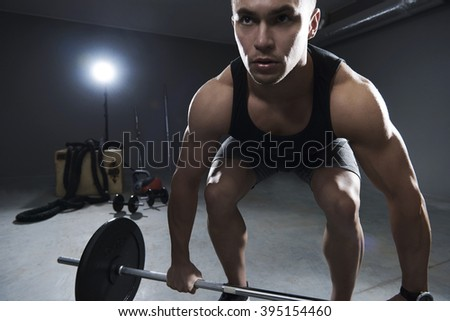 Front view of man lifting some weights - stock photo