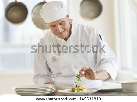 Front view of mature male chef garnishing dish at counter in commercial kitchen - stock photo