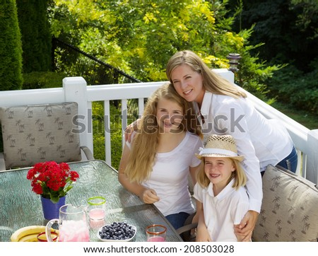 Front view of mature mother holding her two happy daughters while eating breakfast outdoors, during summer time, on patio with woods in background