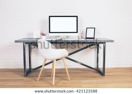 Front view of modern chair and designer desk with blank white computer screen and picture frames on white brick background. Mock up - stock photo