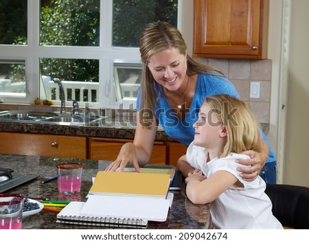 Front view of mom helping her younger daughter doing her homework while in the kitchen  - stock photo