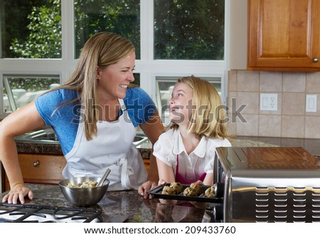 Front view of mother and her young daughter looking at each other as they put raw cookie dough into portable oven