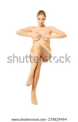 Front view of nude woman sitting on something invisible, covering breast. - stock photo