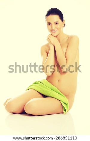 Front view of nude woman sitting, touching chin and wrapped in towel. - stock photo