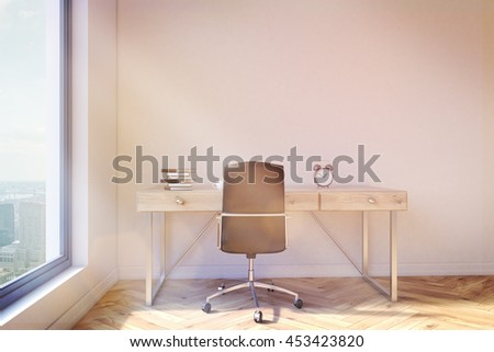 Front view of office interior with pile of books, coffee cup and clock on wooden desktop. Concrete wall, wooden floor, chair and window with New York city view. Toned image, 3D Rendering