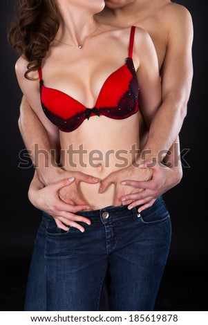 Front view of passionate young couple standing isolated over black background - stock photo