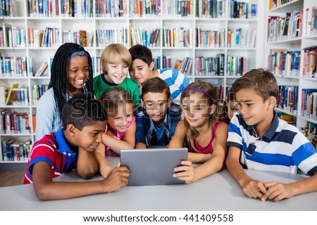 Front view of pupils using tablet pc in library - stock photo