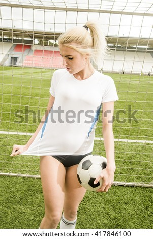 Front view of sexy woman hold ball in hand after penalty kick. Goalkeeper stand in gate behind stadium with seat on background. Female sport idea Empty copy space for inscription - stock photo
