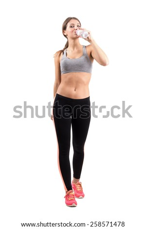 Front view of slim fitness woman drinking water. Full body length portrait isolated over white background. - stock photo