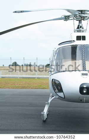 Front view of small, white helicopter at an airport. Only half of helicopter shown. - stock photo