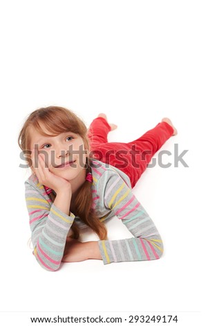Front view of smiling child girl lying on stomach on the floor with head in hands looking away at blank copy space, over white background  - stock photo