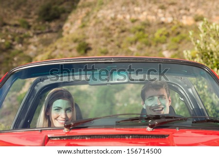 Front view of smiling couple in red cabriolet on a sunny day - stock photo