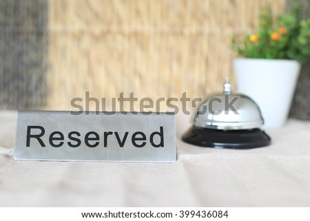 "Front view of stainless ""Reserved"" sign with ringing service bell or hand servant service bell or butler reception service bell in background."