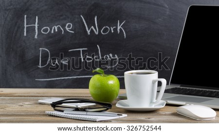 Front view of teachers desktop with laptop, paper, pen, coffee, reading glasses, mouse, cell phone and green apple in front of chalkboard. Layout in horizontal format with copy space.  - stock photo