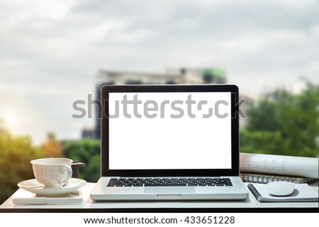 Front view of the laptop and coffee cup is on the work table at office window at construction in morning light  - stock photo