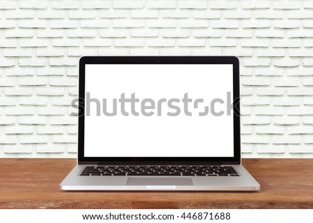 Front view of the laptop is on the work table brick background
