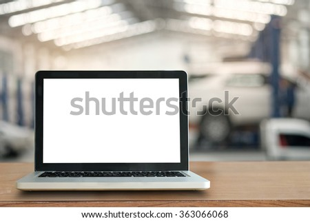 Front view of the laptop is on the work table in garage. - stock photo