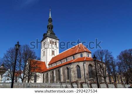 Front view of the medieval former St Nicholas Church, in Tallinn, Estonia, dedicated to Saint Nicholas, on blue cloudy sky background. - stock photo