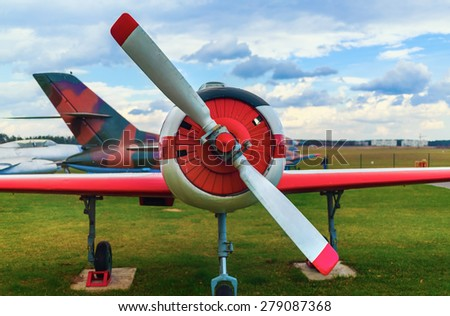 Front view of the part of the fuselage of the old military single-engine plane with a propeller. The airplane parked on the green grass. Selective focus on propeller. - stock photo