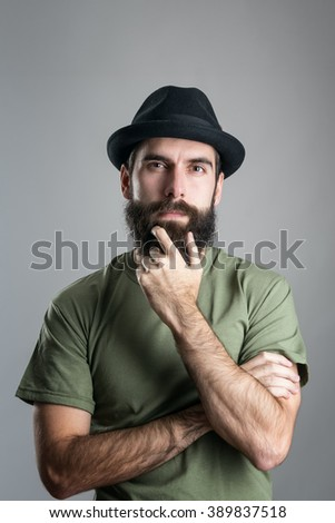 Front view of thoughtful man stroking his beard looking at camera.  Headshot portrait over gray studio background with vignette.  - stock photo