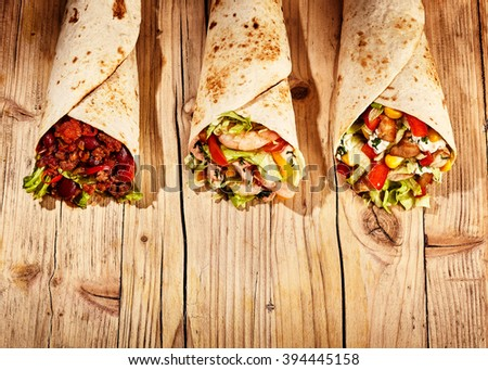 Front view of three meat, bean and vegetable stuffed burritos in baked wheat tortillas on old wooden table table - stock photo