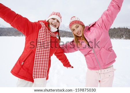 Front view of two joyful young women friends running together across a frozen lake in the snow mountains scenery during a skiing holiday on a sunny winter day, outdoors.