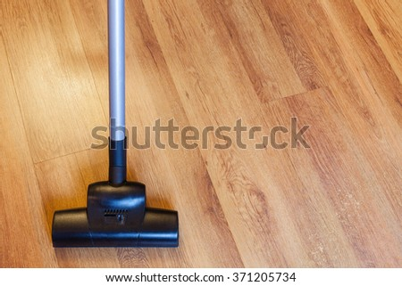 front view of vacuuming of laminate floor by vacuum cleaner at home - stock photo