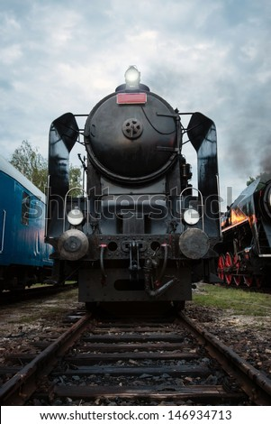 Front view of vintage steam locomotive at railway station with dramatic cloudy sky