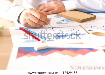 Front view of wooden desktop with male working on business charts and graphs