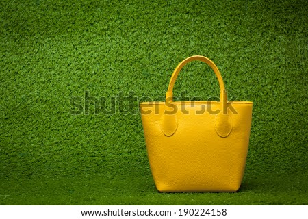 front view of yellow purse on green grass background - stock photo