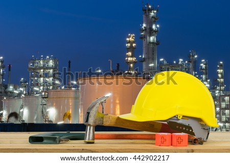 Front view of Yellow Safety Helmet, Hammer, Cutting tools on Oil refinery industry in night