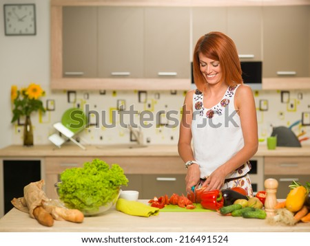 front view of young beautiful caucasian woman standing in kitchen, cutting vegetables and smiling - stock photo