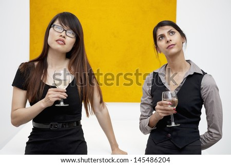 Front view of young females with wine glass looking up in art gallery - stock photo