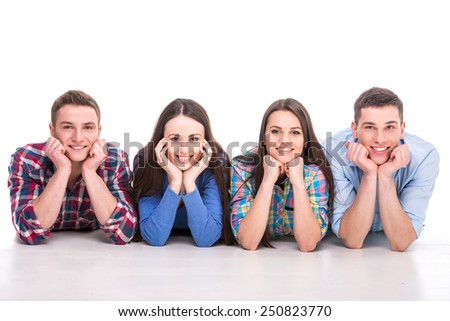 Front view of young people are lying, smiling on floor looking at camera, over white background. - stock photo