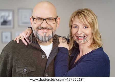 Front view on cute, smiling middle aged male in glasses and blond female Europeans in casual clothing embracing - stock photo