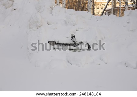 Front view on snow heap covered frozen car at some winter day - stock photo