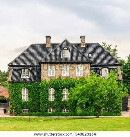Front view on three-story house of light brick with a brown tiled roof. The facade of the house are entwined with green ivy and hedges, Copenhagen, Denmark - stock photo