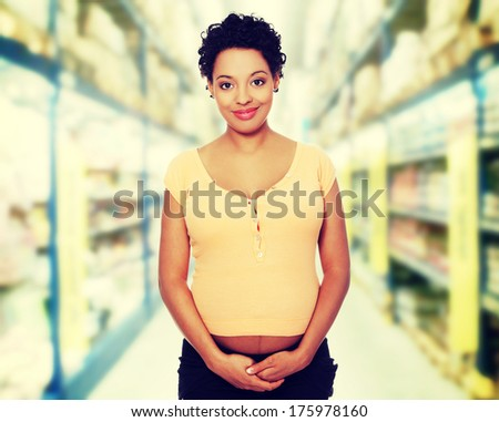 Front view portrait of a beautiful young pregnant woman in store - stock photo