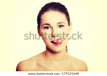 Front view portrait of a young beautiful female caucasian teen, having naked arms, makig a face with her tongue