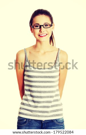 Front view portrait of a young female caucasian teen with glasses on her face smiling to the camera - stock photo