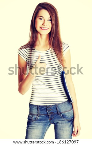 Front view portrait of a young happy female caucasian student holding a notebook and giving a thumb-up