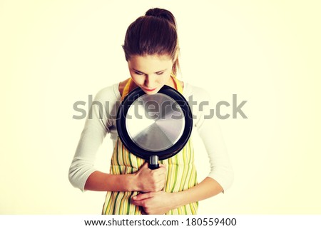 Front view portrait of a young sad caucasian female teen dressed in apron, hugging a frying pan to her chest, looking down, on white. - stock photo