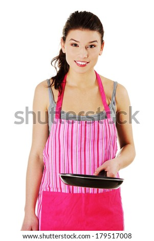 Front view portrait of a young smiling caucasian female teen dressed in apron, holding the frying pan,isolated on white.  - stock photo