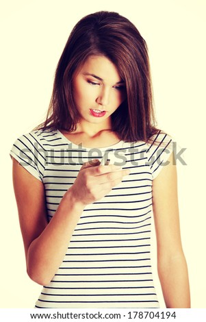 Front view portrait of a young surprised caucasian tenn reading an sms, on white. - stock photo