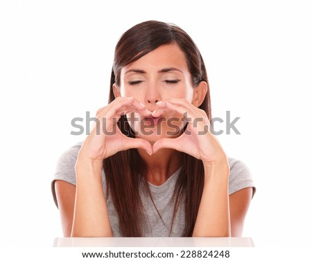 Front view portrait of friendly girl gesturing love and blowing a wish with closed eyes on isolated studio