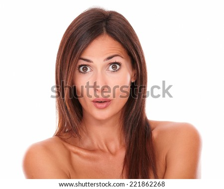 Front view portrait of surprised young woman with brown hair and nude shoulders looking at camera on isolated white background - stock photo