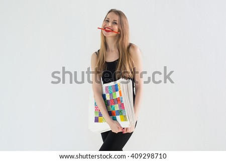 Front view portrait of young female artist holding the hand drawn pictures pack, smiling with a pencil in her teeth. - stock photo