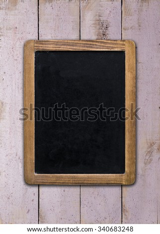 Front view, upright format, of a blank blackboard over a weathered wooden surface - stock photo