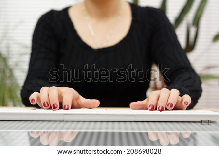 front view  woman is typing on white  keyboard at home - stock photo