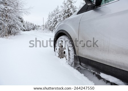 Front wheel in winter tire in snowdrift - stock photo